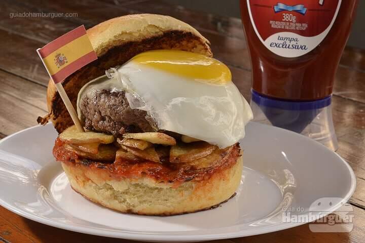 La Rambla Burger: Hambúrguer de 140g com cortes de carnes especiais do Chef, bacon canadense picado na ponta da faca misturado na carne, uma camada de finas batatas rústicas fritas, queijo mozzarella, molho especial com Ketchup Hellmann's e temperos espanhóis e ovo orgânico frito no pão artesanal de brioche. -  R$ 28  - SP Burger Fest