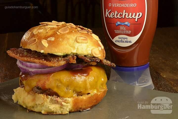 Wild Bite Burger: Pão com amêndoas, hambúrguer de 180g grelhado no carvão, queijo cheddar, cebola roxa, smoked bacon, barbecue de tabaco de corda e molho béarnaise de Wild Turkey Bourbon. - R$ 29 - SP Burger Fest