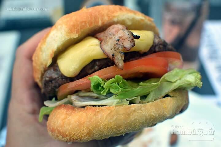Hambúrguer de 150g de Angus Beef, cebolas caramelizadas, bacon glaceada em mel, queijo americano, molho barbecue, alface e tomate por R$ 24,50 - New York Cafe